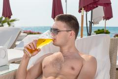 Young man enjoying a cold beer - stock photo