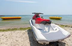Jet ski ashore on a sandy beach - stock photo