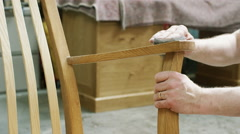 4K Close up on hands of furniture maker finishing off a rocking chair - stock footage
