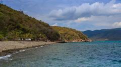 Beach by island village resort surf of azure sea on foreground Stock Footage