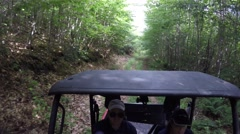 High shot family steering a side by side vehicle in thick green forest Stock Footage