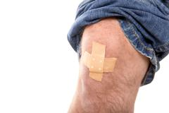 man´s knee glued medical plaster, isolated on white, concept first aid - stock photo