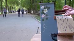 Retro french singer singing & playing barrel organ in public park - song start Stock Footage