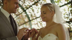 Bride and groom exchange wedding rings in a sunny park Stock Footage