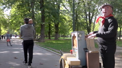 Retro french singer singing & playing barrel organ in public park Stock Footage