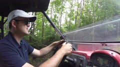 Wide shot of a man steering a side by side vehicle in thick green forest Stock Footage