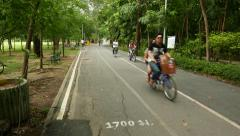 Cyclists rush through park track, POV camera move towards Stock Footage