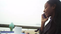 4k Young woman talking on mobile phone and drinking coffee at seafront cafe - stock footage