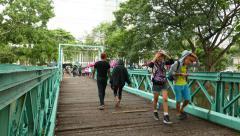 Young citizens walk on footbridge to park, light rain falling Stock Footage