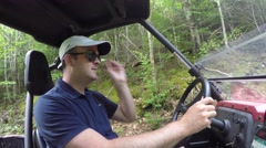 Wide shot of man steering a side by side vehicle in thick green forest Stock Footage