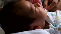 mothers holds her baby as she sleeps - stock footage
