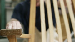 4K Close up on hands of furniture maker finishing off a rocking chair Stock Footage