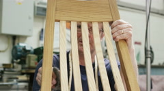 4K Furniture maker in his workshop, putting finishing touches to a rocking chair - stock footage