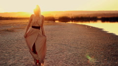 Female model in a beautiful dress dancing on the shore at sunset Stock Footage