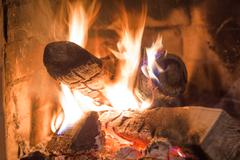 Firewood burning in fireplace fire heat red ashes interior Stock Photos
