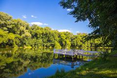 Beautiful pond with a wooden pier water summer day Stock Photos