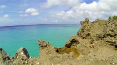 Rocks with crystal clear turquoise sea in background. Tilting Stock Footage