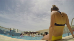 Young woman relaxing pool side at resort - stock footage