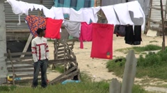 African man stands in front of washing line Stock Footage