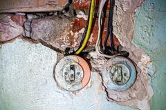 Stock Photo of Two old electric switches in obsolete wall with wires, a lot of copy space