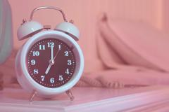 Alarm clock on the bed in bedroom Stock Photos