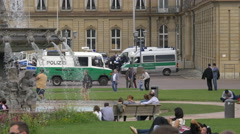 Driving a police van and tourists walking in Palace Square, Stuttgart Stock Footage