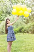 Happy, Freedom, Carefree Young Woman with Yellow Balloons at beautiful Summer Stock Photos