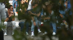 Tourists sitting down, drinking and talking in a square in Stuttgart Stock Footage