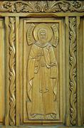 Wooden door with carved representation of Saint Anthony - stock photo