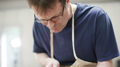 4K Furniture maker in his workshop, concentrating as he works - stock footage