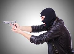 Young thug with gun isolated on white - stock photo