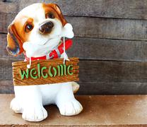 ceramic welcome dog on wooden background still life - stock photo