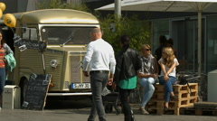 Family sitting next to a beverage van and people passing by, Stuttgart Stock Footage