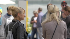 Young women talking and laughing while other people are passing by, Stuttgart Stock Footage