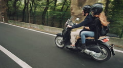 Young male riding a scooter with girlfriend shows shaka sign Stock Footage