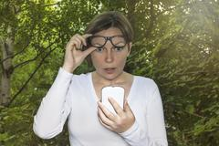 Surprised woman looking at phone - stock photo