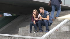Couple sitting on stairs and eating ice cream at Palace Square, Stuttgart Stock Footage