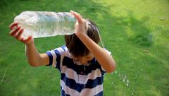 Boy pours the water from a plastic bottle, boy takes a shower Stock Footage