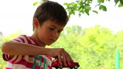 Boy dreams of a car, boy playing with a toy car, Land Cruiser Stock Footage