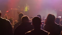 Crowd audience in lumiere swaying hands up in air to performer on concert stage - stock footage