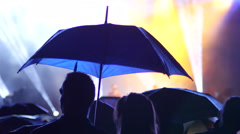 Listen to music concert in lumiere silhouettes of spectators under umbrella - stock footage
