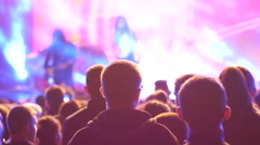 Crowd audience listen to performer on a concert stage in flashing light lumiere Stock Footage