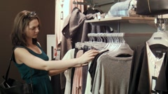 Girl is looking for a suitable skirt and blouse clothes Stock Footage