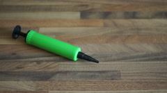 4k Green Balloon Pump rolls and lies still on wooden table top Stock Footage