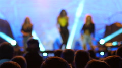 Spectators silhouettes listening to singer girl on concert stage in lumiere Stock Footage