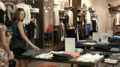 Two young girls choose clothes in shop Stock Footage