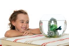 Girl is watching fish in an aquarium Kuvituskuvat