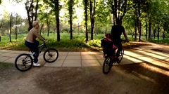 Happy People Riding Bicycles In Green Park At Sunny Day - stock footage