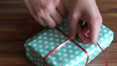 4K Putting red string around a paper wrapped present/gift Stock Footage