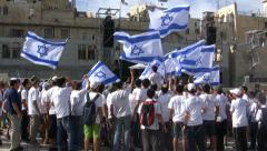 Young Jewish Yeshiva students dance with flags Western Wall, Jerusalem Israel Stock Footage